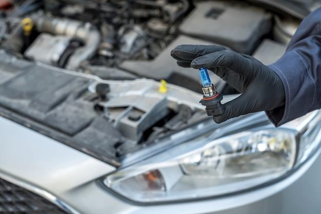 자동차 헤드 라이트에 대 한 할로겐 led 전구를 설치하는 수리 남자 손. 자동 조명 램프 기술