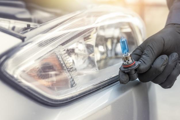 Ремонтник вручную устанавливает галогенную светодиодную лампу для автомобильных фар
