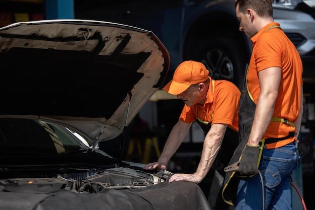 Repair man worker polishing automobile car body in garage