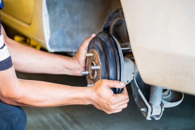Repair mechanic hands during maintenance work to brake system of car, man fixing repairing car rotor spindle hub wheel automobile vehicle parts in garage
