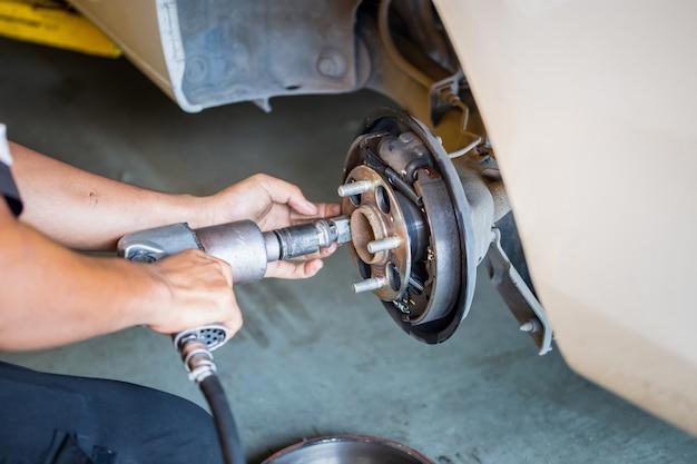 Repair mechanic hands during maintenance work to pneumatic gun to loosen a wheel nut changing tyre of car, man fixing repairing car rotor spindle hub wheel automobile vehicle parts in garage
