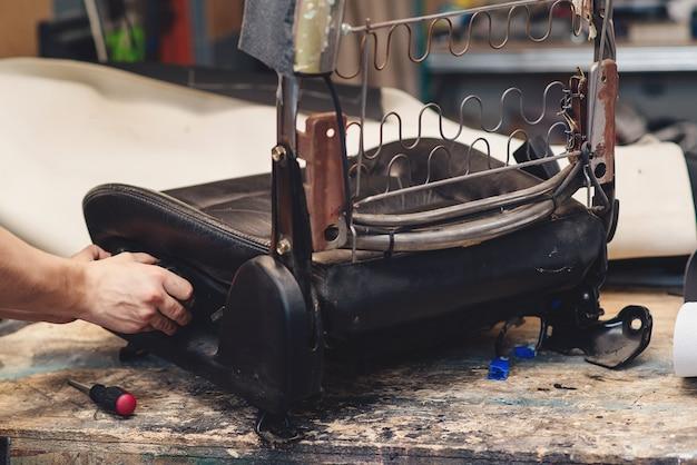 Ремонт старого автокресла. руки автомеханика использует инструменты. рабочие руки мужчины в автосервисе, крупным планом.