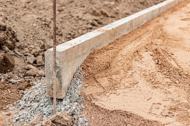 Ремонт тротуара с установкой бордюрного камня. укладка тротуарной плитки в пешеходной зоне города. движение бетонных бордюров.