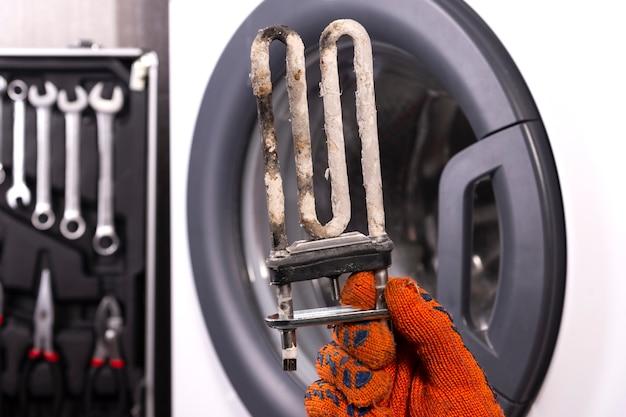 洗濯機の修理。硬水のコーティングで覆われた乱流電気ヒーターの修理工の手。洗濯機の電気ヒーターの交換