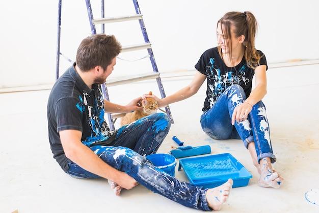 Ремонт домашних животных и концепция людей пара с кошкой собирается красить стену, которую они смешивают