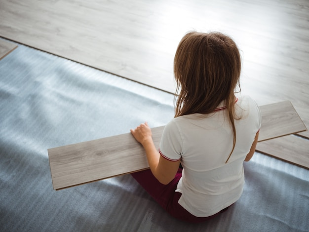 The repair process in the apartment. the girl performs the laying of the laminate