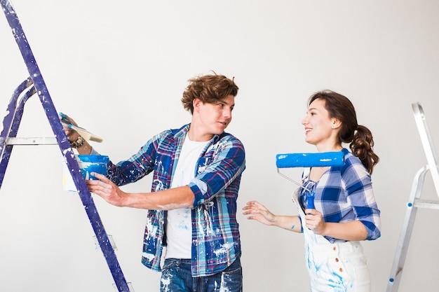修理、リノベーション、愛のカップルのコンセプト – 若い家族が一緒に模様替えをし、壁に絵を描き、笑い合う。