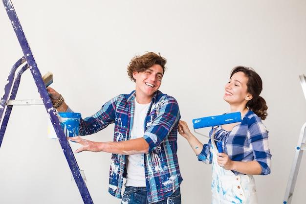 수리, 개조 및 사랑의 부부 개념-젊은 가족이 재 장식을하고 벽을 칠합니다.