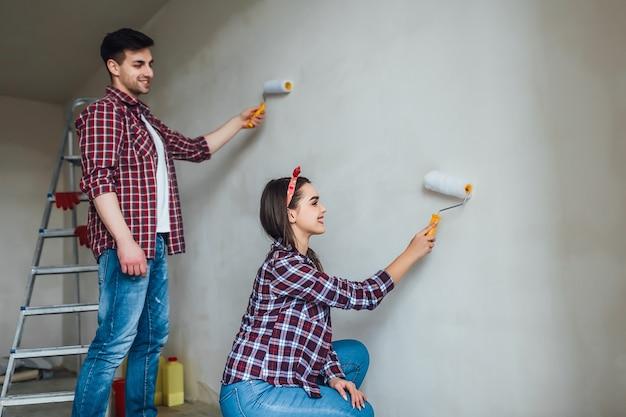 修理、リフォーム、愛のカップルのコンセプト-若い家族が一緒に修理と壁の塗装をして笑っている