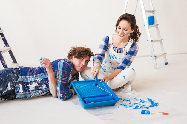 修理、リノベーション、人々のコンセプト – 壁にペンキを塗り、色とブラシを用意する夫婦。