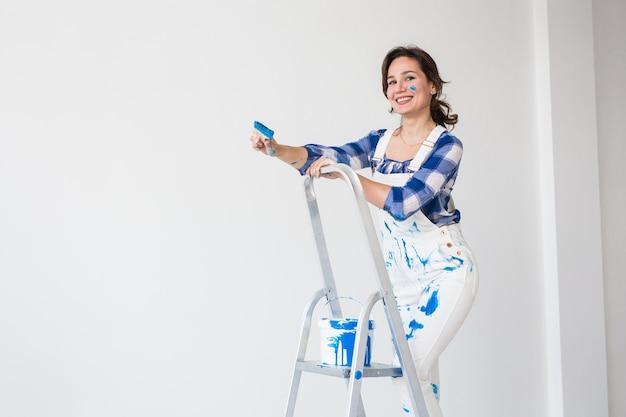 Концепция ремонта, ремонта и людей - счастливая молодая женщина красит стену дома с копией пространства