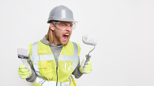 Repair and renovation concept. annoyed irritated male builder exclaims loudly holds painting brush and roller