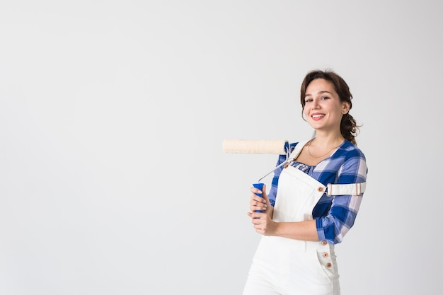 Repair, renovation, new home and people concept - beautiful woman paints the wall during redecoration with copy space