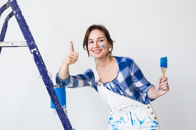 Repair, renovation, worker and people concept - happy young woman paint wall at home, showing us thumbs up.