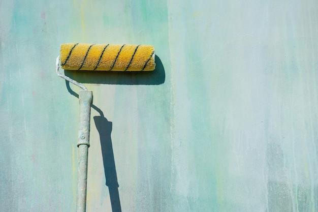 修理、壁を塗るためのローラーは青い壁の上に立っています。修理、染色、内装工事。更新コンセプトのポスター。プロのコンセプト