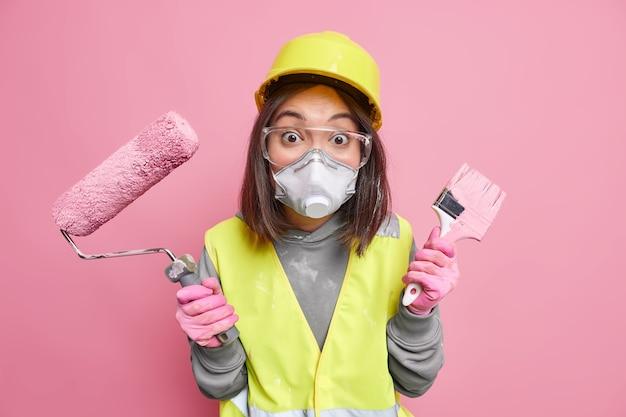 修理サービスと建設コンセプト。作業服保護メガネマスクとヘルメットに身を包んだ驚いた熟練した女性ビルダーはローラーとペイントブラシを保持します