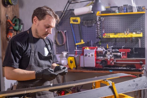 修理、サービス、人のコンセプト-パラフィンをこすってスキーを修理する男性。