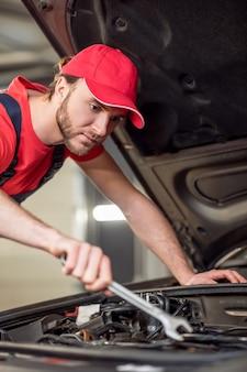 修理サービス。オーバーオールと赤いキャップの真面目な若いひげを生やした男が車を修理するフードの近くにソケットレンチで曲がって立っている