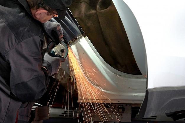 Ремонтник исправит поврежденную машину. работа с углошлифовальной машиной для закрепления металлического корпуса.