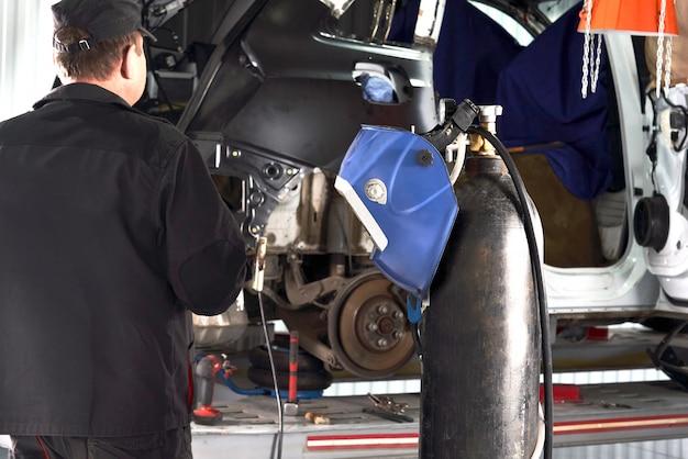 수리 서비스 작업자 수정 손상된 자동차. 금속 몸체를 고정하기 위해 앵글 그라인더 작업.