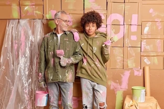 수리 시간 및 팀 작업 개념. 혼합 된 인종 여자와 남자는 도구와 함께 서서 바쁜 페인팅 집 벽을 함께 실내에서 거실 작업을 개조합니다. 두 명의 전문 화가