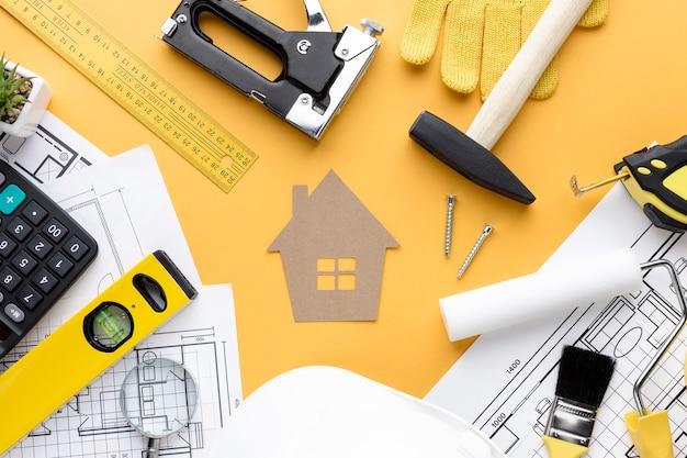 Инструменты для ремонта и синяя печать вокруг картонного дома