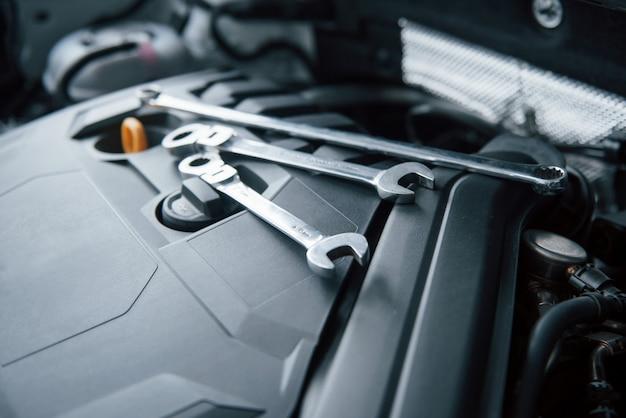 Strumenti di riparazione sdraiati sul motore dell'automobile sotto il cofano