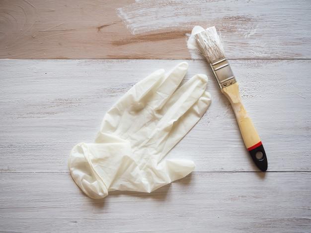 Ремонтные работы по покраске. перчатки и кисточка на фоне не красятся до конца пола.