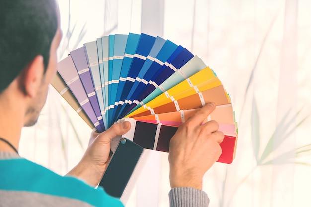 パレット上の絵の具の色を選択するための修理作業。セレクティブフォーカス。人。
