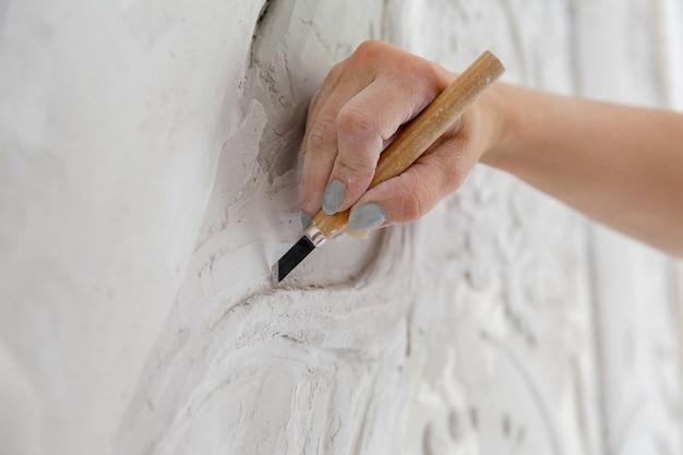 수리 작업 흐름, 끌 도구를 가진 여성이 벽에 옅은 패턴을 새깁니다.
