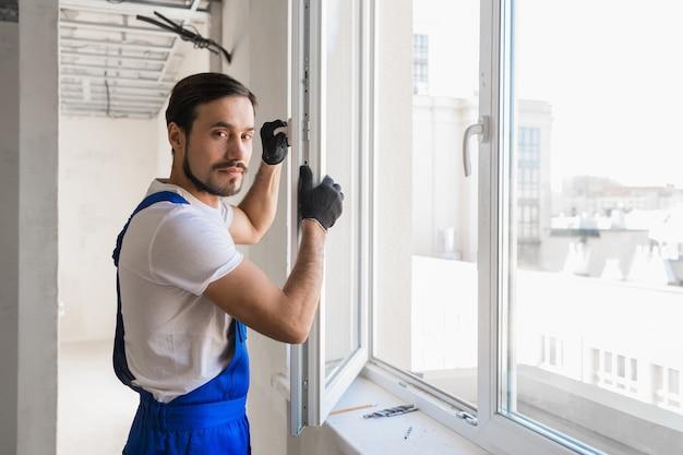 Ремонтник в спецодежде строит у окна и смотрит в камеру
