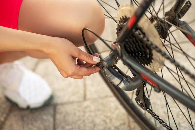 自転車の修理。自転車の車輪をチェックする明るいスポーツウェアの若いサイクリスト