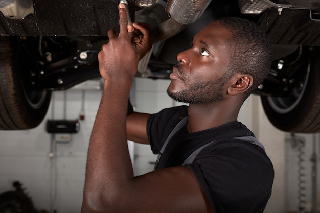 Repairing in action. hardworking guy employee in uniform works in the automobile salon