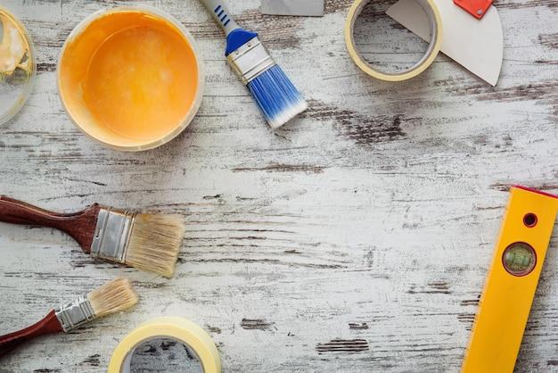노란색 페인트, 브러쉬 및 페인트 테이프로 회색 나무 표면에 수리 도구 키트