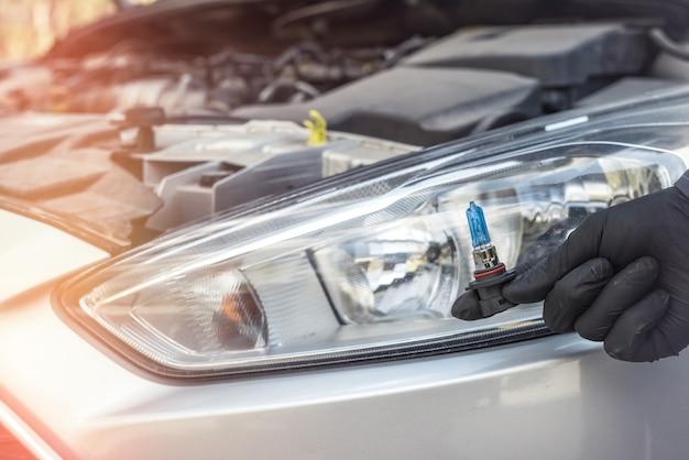 Autoshop의 수리공은 교체를 위해 새 자동차 전구를 보여주고 백그라운드에서 헤드 램프를 표시합니다. 램프 라이트