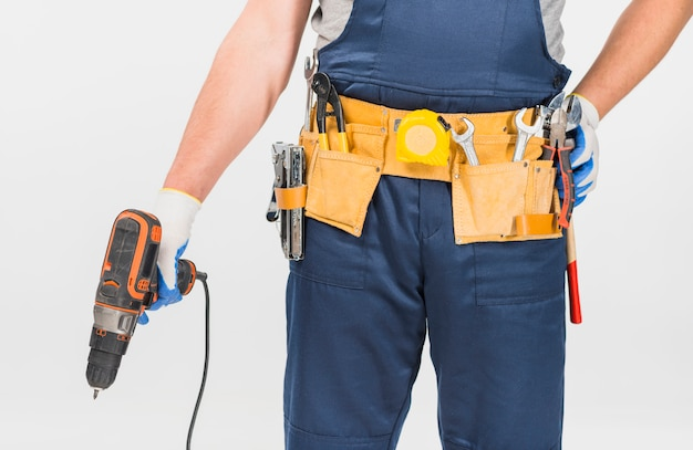 Repairman in blue overall holding drill
