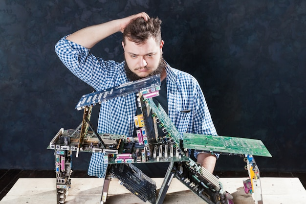 Мастер по ремонту строит карточный домик из материнских плат. инженер производит диагностику электронных компонентов. сломанное компьютерное оборудование