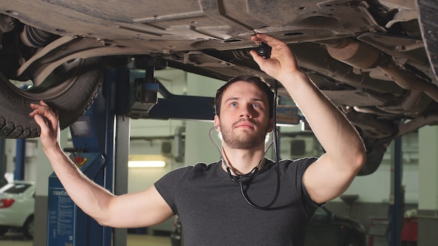 Repairman of car workshop is standing under lifted automobile and examining details.