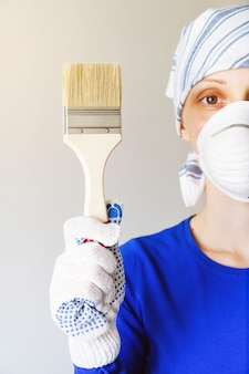 Repairman, carpenter, employee, girl or woman in protective gloves holding a new brush.