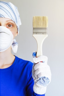 Repairman, carpenter, wage worker, woman or girl in protective gloves and mask holds a new clean paintbrush, looks in cell. the concept of home and professional repair, construction.
