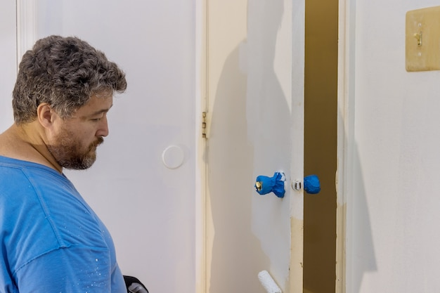 Ремонтник плотник работает покраска деревянной двери