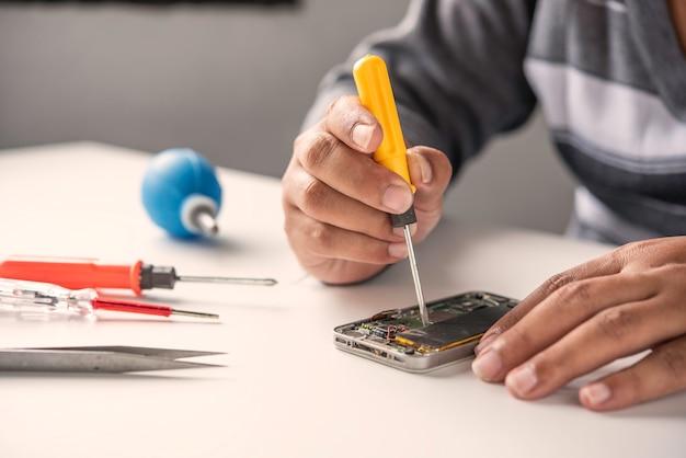 Repairman disassembling repairman disassembling smartphone with screwdriver.