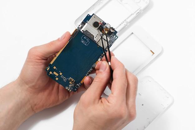 핀셋으로 스마트 폰을 분해하는 수리공