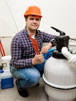 Инженер-ремонтник позирует у циркуляционной системы высокого давления с красными плоскогубцами