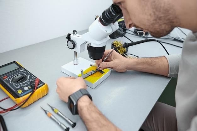 実験室で顕微鏡下で携帯電話のマザーボードを調べる修理工