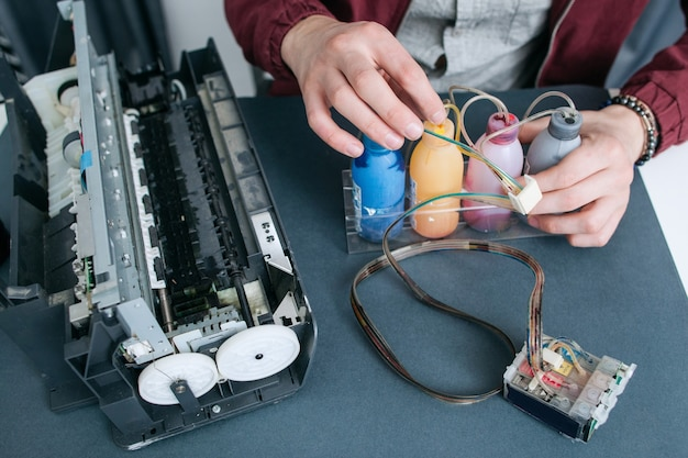 Repairman fixing ciss in office printer