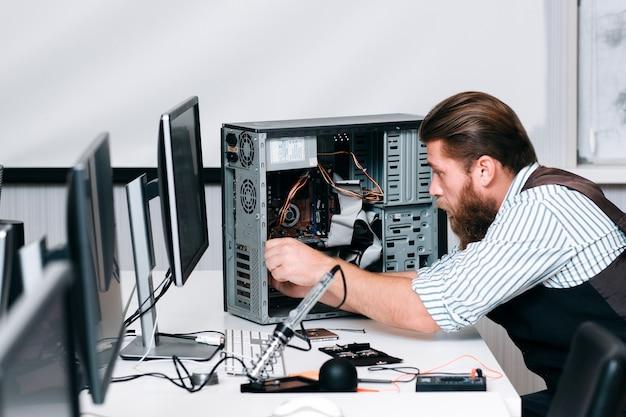 수리공은 컴퓨터 장치의 구성 요소를 고정합니다. 수리점에서 cpu를 조립하는 수염 엔지니어. 전자 혁신, 수정, 개발 개념