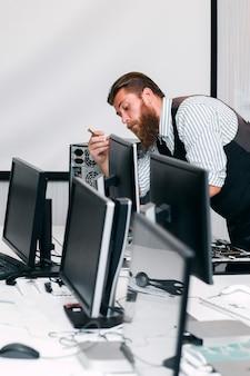 Ремонтник, ремонтирующий компьютерный монитор в офисе. программатор крепления экрана для работы в открытом космосе. программирование, ремонт, концепция ремонта