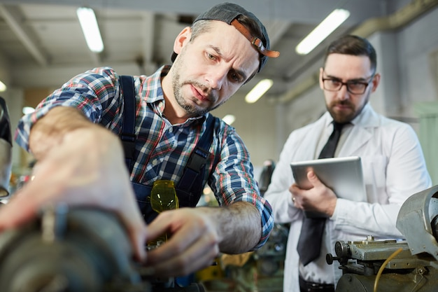 Repairman fixing machines at factory