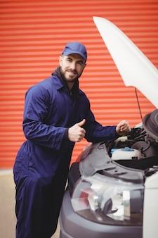Repairman fixing  a van with thumbs up